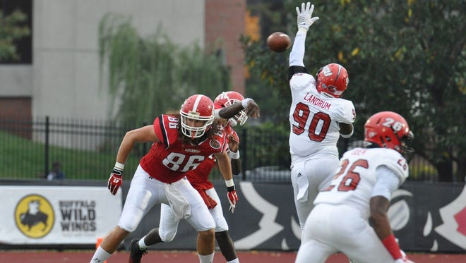 Timarious Mitchell throws the ball as a Jacksonville State defender attempts to block the pass.