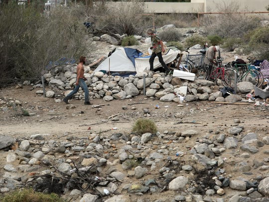 Homeless men camped behind the closed Rock Garden Bar & Grill in Palm Springs on Wednesday.