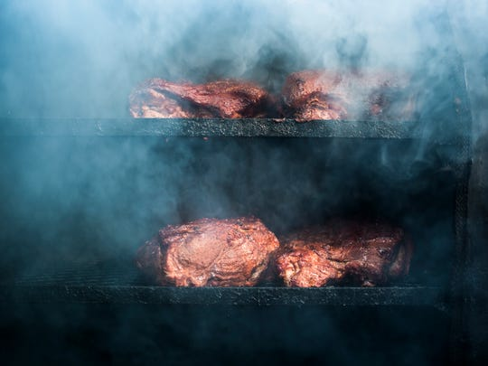 The Smokin' Grill prepares their Boston pork butt in a smoker during the Pig in the Park BBQ Festival and Cook-off last year.