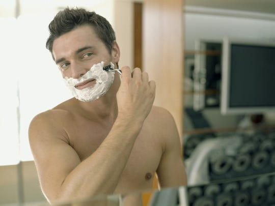 A man shaving in the mirror.