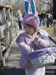 Myla Garza carries her basket collecting Easter eggs