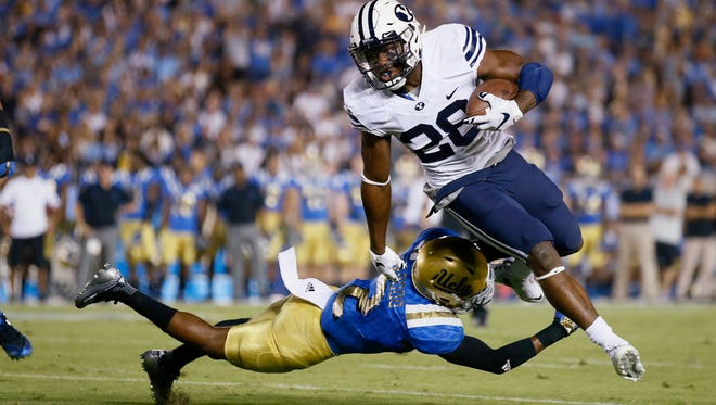 BYU running back Adam Hine breaks a tackle attempt from UCLA's Jaleel Wadood on his way to scoring a touchdown during the first half of an NCAA college football game Saturday, Sept. 19, 2015, in Pasadena, Calif.
