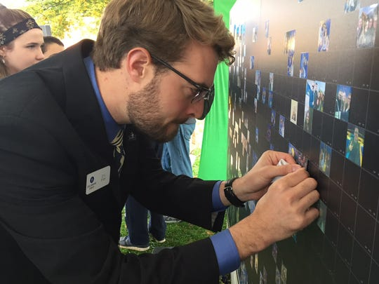 DV Starr posts a photo on a mosaic wall during an event Thursday afternoon at the University of Delaware to mark the start of an endowment campaign seeking to raise $750 million for the university.