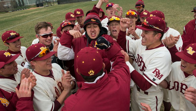 The Rocky Mountain High School baseball team celebrates with head coach Scott Bullock after winning a game against Fort Collins High School on Saturday, April 7, 2018, at Rocky Mountain High School in Fort Collins, Colo.