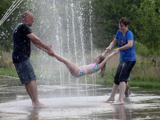Chris Langford, left, and Allison DeZarn, right, swung Kristen Blandford, 8, on the sprayground as they visited The Park Lands of Floyds Fork.July 15, 2015I love the spontaneous joy and simplicity in this moment.
