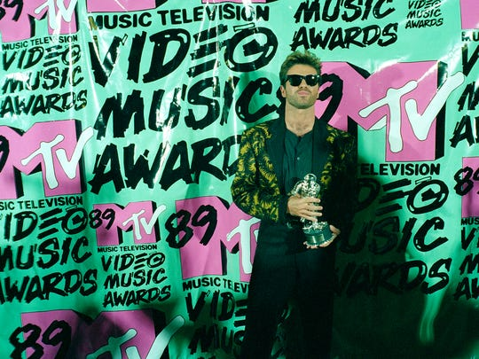 "FILE - In this Wednesday, Sept. 6, 1989 file photo, musician George Michael holds his trophy after winning the 1989 Video ""Vanguard Award"" for his ""Father Figure"" video during the MTV Music Awards at the Universal Ampitheatre in Universal City, Calf. Michael, who rocketed to stardom with WHAM! and went on to enjoy a long and celebrated solo career lined with controversies, has died, his publicist said Sunday, Dec. 25, 2016. He was 53. (AP Photo/Alan Greth)"