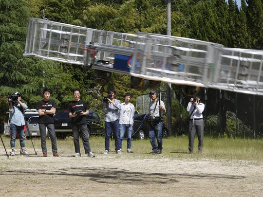 "In this 2017, file photo, Tsubasa Nakamura, project leader of Cartivator, third from left, watches the flight of the test model of the flying car on a former school ground in Toyota, central Japan. The Japanese government has started a ""flying car"" project, bringing together more than a dozen companies, including All Nippon Airways, electronics company NEC, Toyota-backed startup Cartivator and Uber, the ride-hailing service."