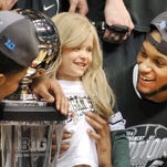 Lacey Holsworth of St. Johns celebrates the MSU Big Ten Championship win with Garry Harris (L) and Adreian Payne March 16.