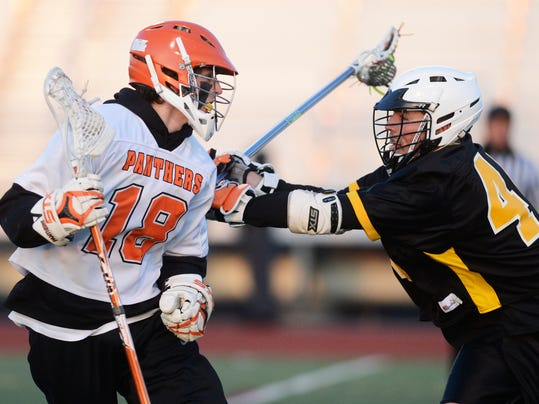 Central York's Ian Desenberg, left, works around Red Lion's Gary Rhoades on Wednesday night. Desenberg scored four goals in the third period to help the Panthers win, 14-9. (Daily Record/Sunday News -- Kate Penn)