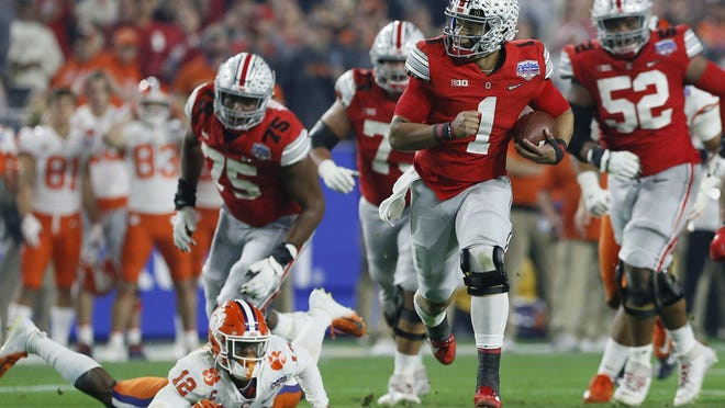 Ohio State quarterback Justin Fields breaks away from Clemson safety K'Von Wallace at the Fiesta Bowl on Dec. 28 in last season's College Football Playoff semifinals.