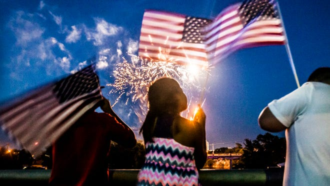 Andres Sanchez (left), Andrea Sanchez (center), and Kobe Moore wave U.S. flags while they watch the San Angelo Pops Symphony fireworks show July 3, 2014.