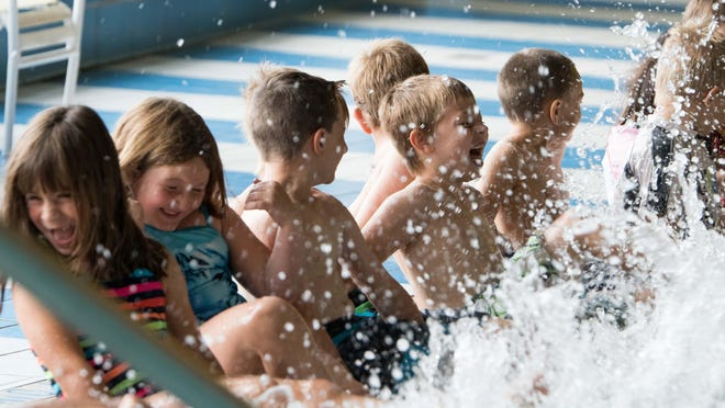 Kids splash in the pool before they start their swim lessons at Full Blast Thursday morning.