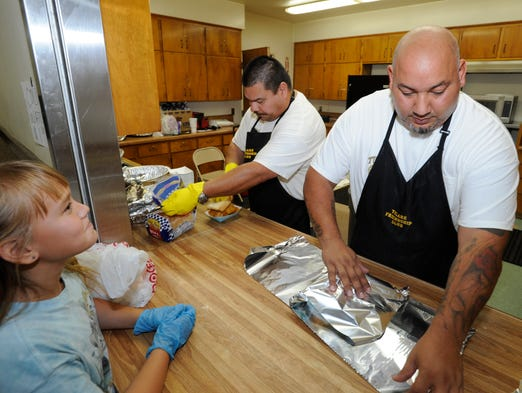 Rey Serrano, his daughter Sariah Serrano and Alex Garcia of the Tulare Friendship Club serve food during the third annual Juneteenth Celebration and Fish Fry on Saturday at the Claude Meitzenheimer Community Center in Tulare.
