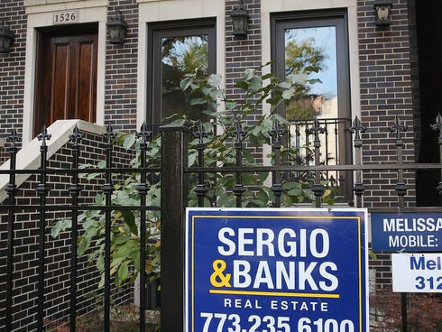 A real estate sign hangs on a fence in front of a home in the Wicker Park neighborhood  in Chicago.
