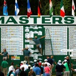 Golf patrons watch the main Masters scoreboard as workers perform updates during second round play of the Masters golf tournament on Friday at the Augusta National Golf Course in Augusta, Ga.