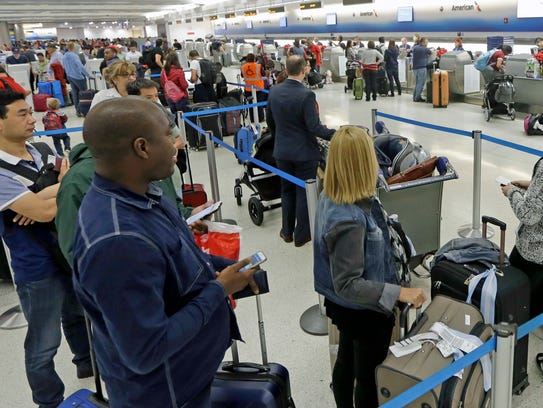 Passengers stand in line to check in their luggage