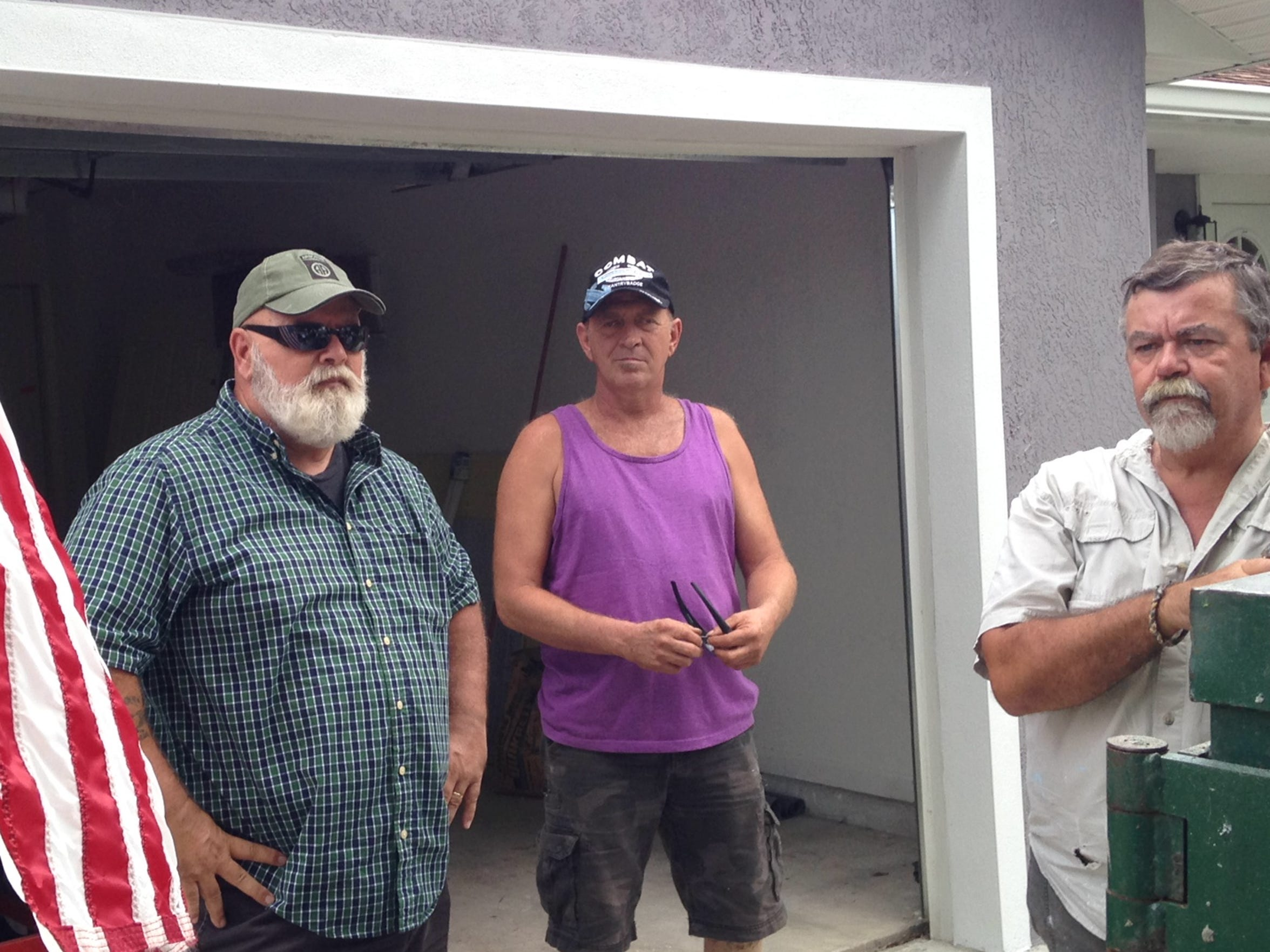 David Isnardi, left, Stephen Hamrick, center, and Bob Williams discuss work plans for the finishing touches to the house Hamrick received from the city and the Space Coast Paratroopers Association.