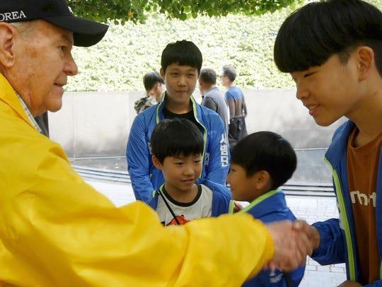 Korean War veteran Charles Berry shakes hands with