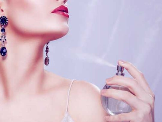 A woman sprays herself with perfume.