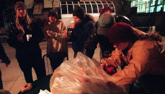 In this 1993 Coloradoan file photo, Colorado State University students warm up with bagels and hot chocolate before zipping into sleeping bags outside the Lory Student Center during a sleep out event.