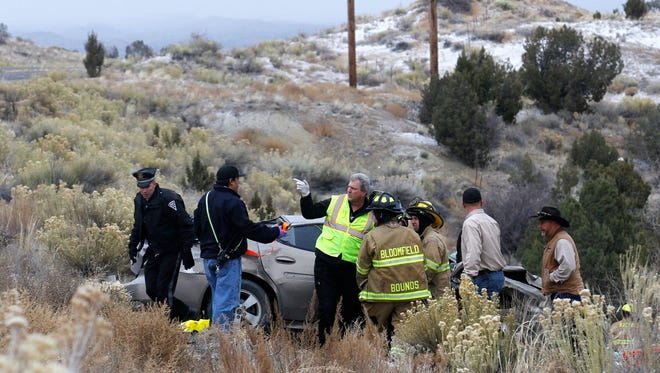 Emergency crews respond to a car crash on Monday north of the Hilltop Giant gas station on U.S. Highway 550.