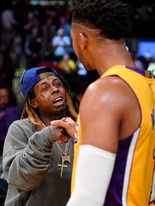 Rapper Lil Wayne, left, talks with Los Angeles Lakers guard D'Angelo Russell after the Lakers defeated the Brooklyn Nets in an NBA basketball game, Tuesday, Nov. 15, 2016, in Los Angeles. The Lakers won 125-118. (AP Photo/Mark J. Terrill)