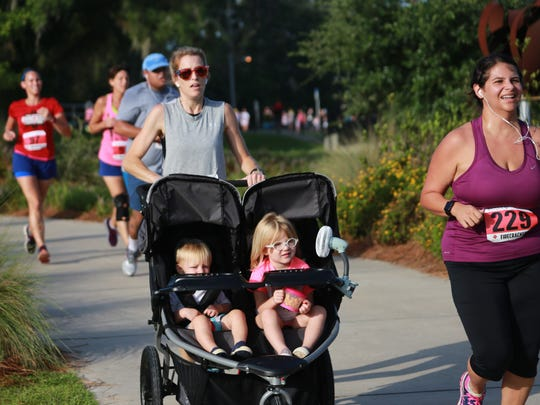 A woman pushes two children in a stroller during last