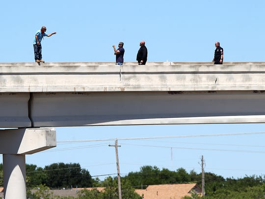 San Angelo police officers negotiate with a man threatening to jump from atop of N Loop 306 at the Pulliam exit overpass from N U.S. HWY 67 Thursday, May 4, 2017. Police were able to talk the man down safely.