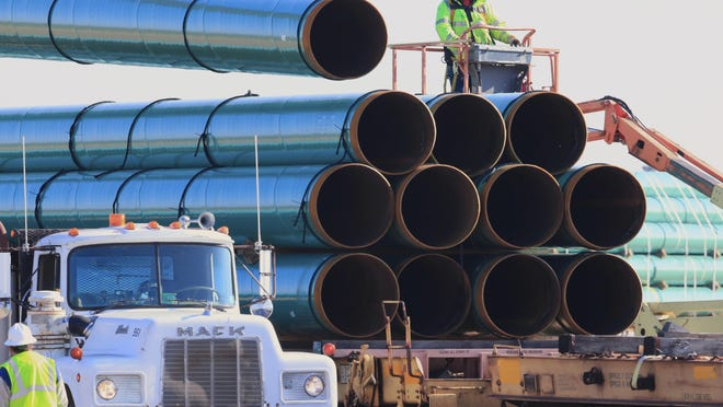 Workers unload pipes in Worthing, S.D., in 2015 for the Dakota Access oil pipeline. A federal judge ordered the U.S. Army Corps of Engineers on March 25, 2020, to conduct a full environmental review of the pipeline, nearly three years after it began carrying oil.