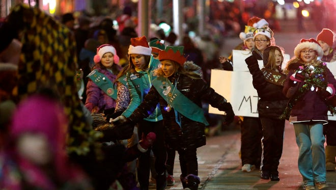 Girl Scouts give high fives to the crowd as they walk down College Avenue during The 45th Annual Downtown Appleton Christmas Parade Tuesday, Nov. 24, 2015, in Appleton, Wis.