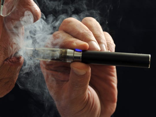 In this photo illustration, a smoker puffs on an e-cigarette. E-cigarettes are being touted as a safe alternative to traditional lighted tobacco products. Studies are looking at the chemical makeup of the secondhand vapor which is breathed out like smoke. (AP Photo/Wichita Falls Times Record News, Torin Halsey) ORG XMIT: TXWIC103