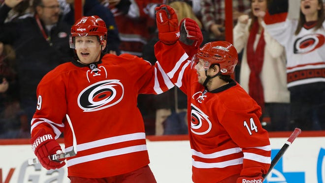 Jan 31, 2014; Raleigh, NC, USA; Carolina Hurricanes forward Nathan Gerbe (14) celebrates with forward Jiri Tlusty (19) after scoring a goal against the St. Louis Blues at PNC Arena.