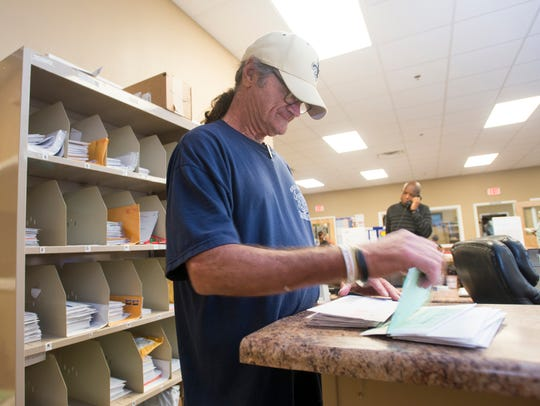 Volunteer Frank Marinin sorts client mail at the Waterfront