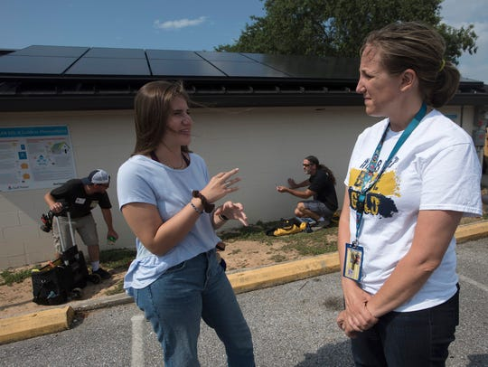 Gulf Breeze High School senior Addie Sims and science teacher Erin Cosky talk Friday about the school's solar panel project.