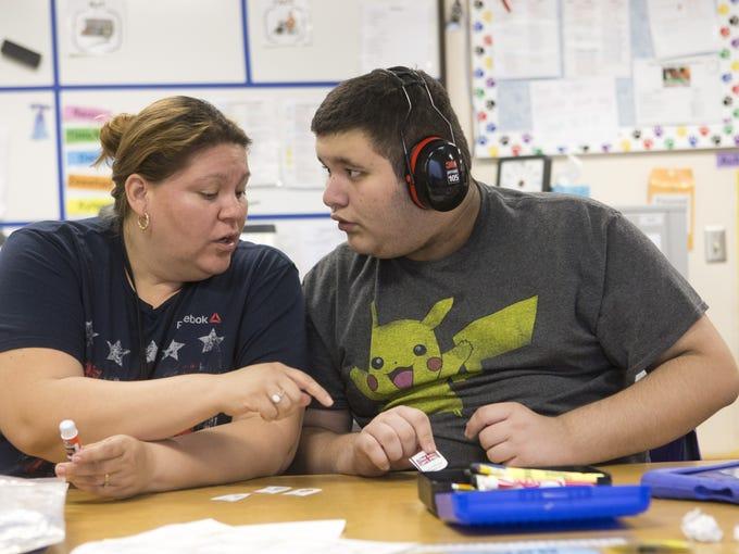 Teacher's Aide Monica Garcia works with Seth Fischer,