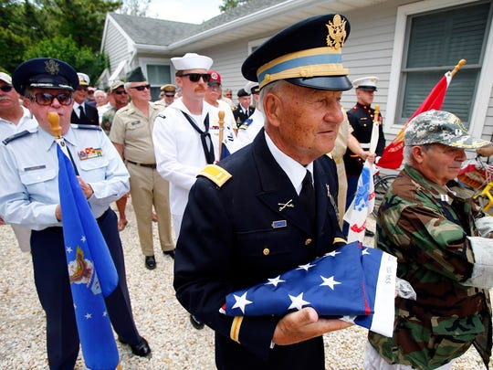 Army veteran Bob Morzek, Normady Beach, holds the flag as he prepares to march with other veterans to the flag raising ceremony on 6th Avenue in the Normandy Beach section of Brick Township, NJ, Monday, July 4, 2016.