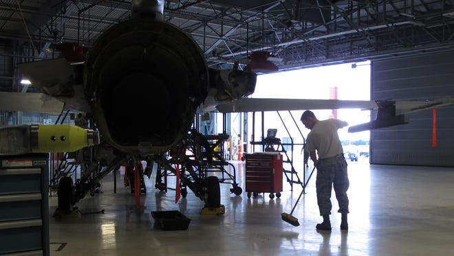 Maintenance workers with the Vermont Air National Guard clean up during routine maintenance on an F-16 on Friday afternoon at Burlington International Airport.