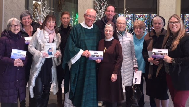 Each month, a Saving Other for Archie Mass is held at the St. Catherine of Alexandria and St. Joan of Arc cluster parish. Among those at a recent Mass are (from left) Jacky Morgan, Kelly Morgan, Scotti Keepman, Ricki Hopper, the Rev. Mike Strachota, Sister Ellen Pollack,Andy Badura, Pat McHugh, Ellen Heitman, Sister Beatrice Knipple and Lauri Badura.
