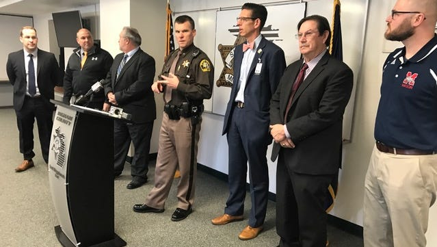 Ingham County Sheriff Scott Wriggelsworth (center) was joined by local school officials at a news conference Friday about a plan to boost police presence in out-county schools.