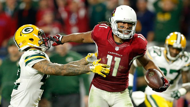 Larry Fitzgerald of the Cardinals stiff-arms the Packers' Morgan Burnett on his winning touchdown in overtime.