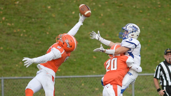 Cherokee's Jackson McIntyre nearly intercepts a pass as his teammate Devin Ibarrondo wraps up Williamstown's Nick DeRosa during a 24-17 win on Saturday.
