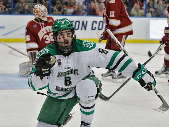 North Dakota forward Nick Schmaltz (8) reacts after scoring against Denver during final seconds of an NCAA Frozen Four men's college hockey semifinal, Thursday, April 7, 2016, in Tampa, Fla. (AP Photo/Chris O'Meara)