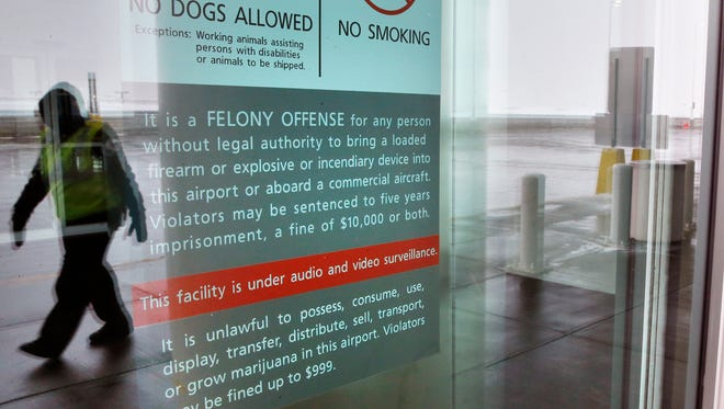 A security officer walks near a notice prohibiting marijuana possession at Denver International Airport on Jan. 27, 2014. Carrying marijuana through airport security in Colorado may get the pot confiscated, but there appears to be little danger of legal repercussions.