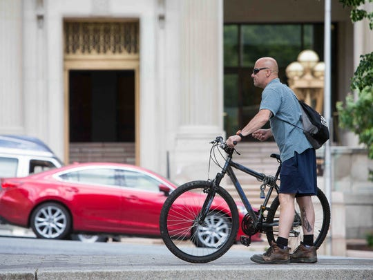 A rider hops on his bike in Rodney Square in Wilmington.