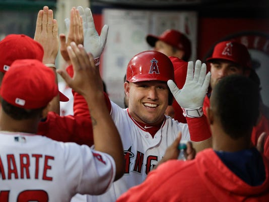 Los Angeles Angels' Mike Trout, center, is greeted by teammates after he scored on a single by Albert Pujols during the first inning of a baseball game against the Oakland Athletics, Thursday, April 27, 2017, in Anaheim, Calif. (AP Photo/Jae C. Hong)
