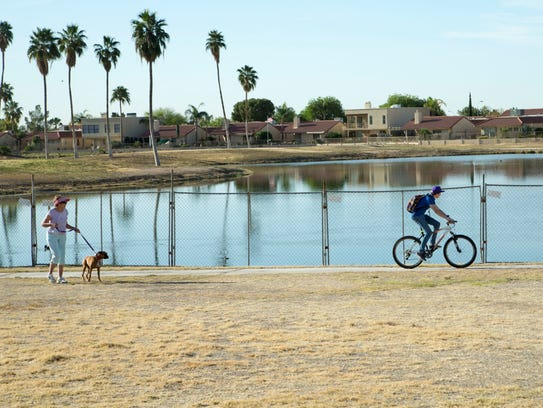 Linda Overby (left) walks her dog near shuttered Ahwatukee Lakes Golf Club in April 2014.