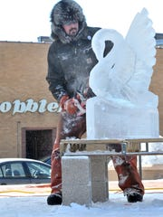 Steve Brandt of Cedarburg carves a swan sculpture out of a ice block during Winter Fest 2012 at The 400 Block in downtown Wausau.