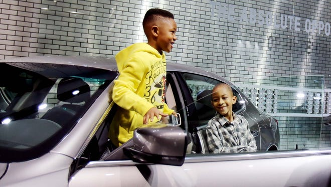 Marvin Hartfield , 7, of Fraser, left,  jumps out of a Maserati as his cousin Solomon Spann, 6, is having fun with him during the 2015 North American International Auto Show.