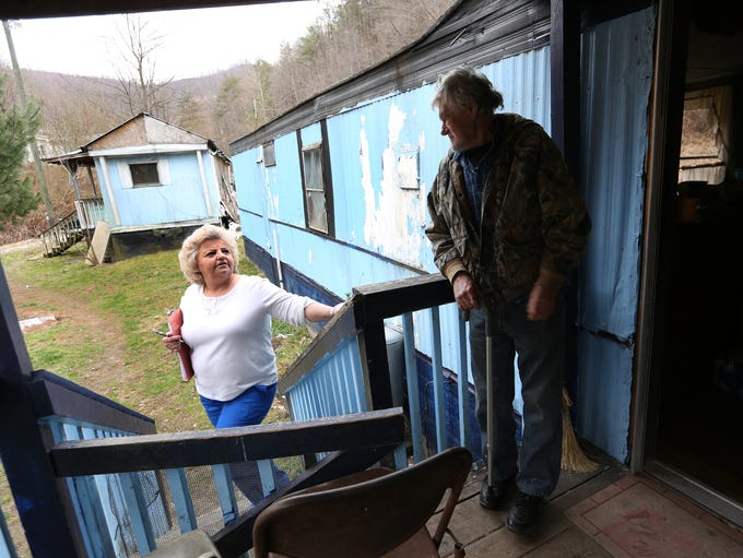 Eula Hall Health Center pharmacy technician Linda Stratton approaches Donald Ray Hall to deliver medicine to his wife, Emma, in Floyd County, Ky. The remoteness of the region makes it difficult for patients to access their medicines, so sometimes clinic staffers bring them to patients' homes.