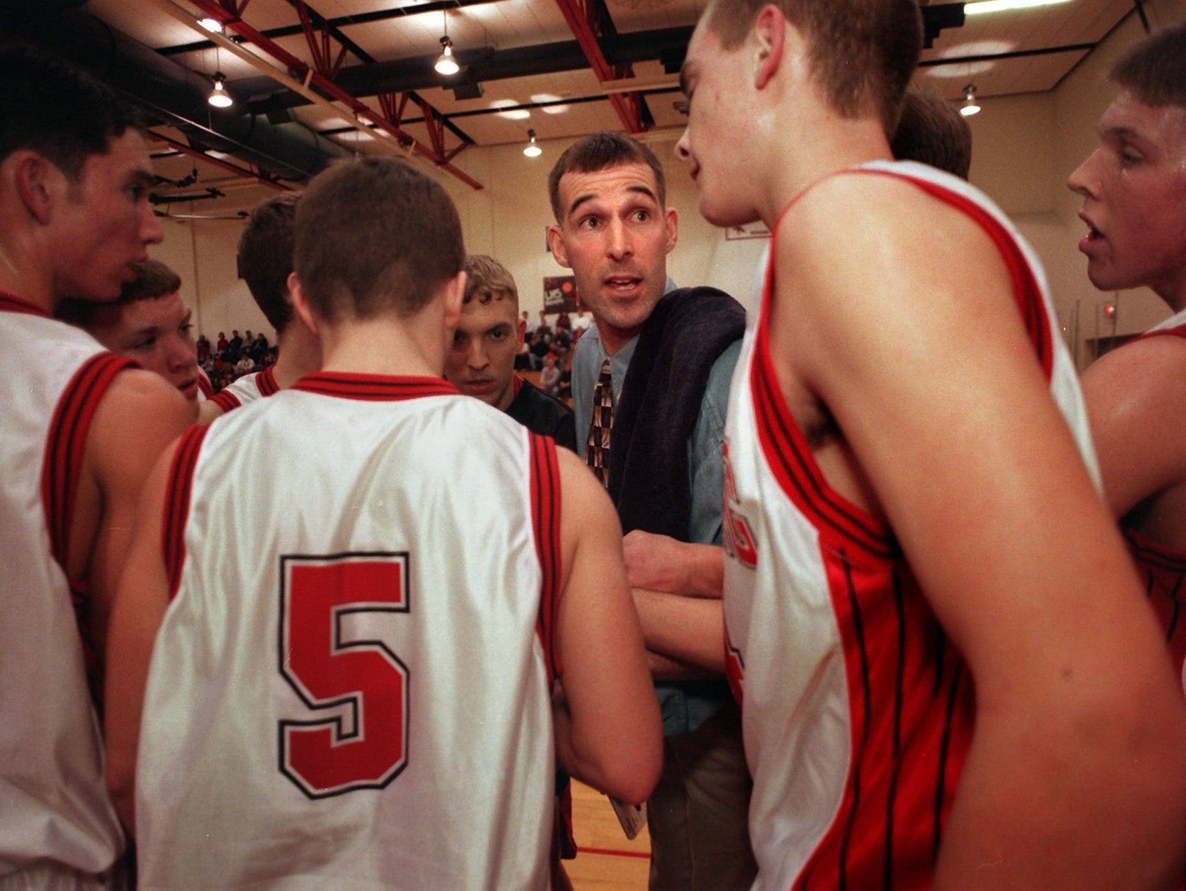 Greg Mitchell, who was then the Laingsburg boy's basketball coach, talks with his team during a 1999 game against Pewamo-Westphalia.